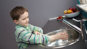Eau du robinet de versement de garçon dans un verre Image libre de droits
