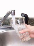 eau du robinet en verre remplissante Photographie stock libre de droits