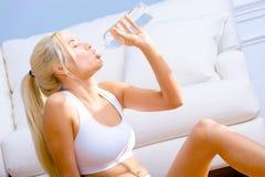 Eau en bouteille potable de jeune femme Image libre de droits