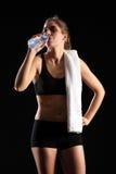 Eau en bouteille potable de jeune femme après exercice Images stock