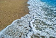 Eau et sable de mer sur un coucher du soleil Images libres de droits
