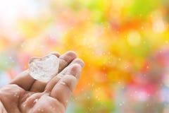 Eau glacée de plaine de forme de coeur en main et backgroun romantique de bokeh Images libres de droits