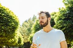 Eau potable d'homme adulte d'une bouteille dehors photo stock