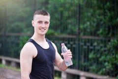 Eau potable d'homme bel d'athlète Photographie stock libre de droits