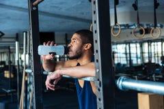 Eau potable d'homme en bonne santé de forme physique dans le gymnase images stock