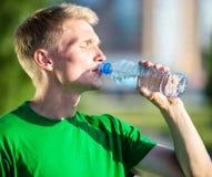 Eau potable d'homme fatigué d'une bouteille en plastique Photographie stock