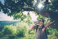Eau potable d'homme sous l'arbre Image stock