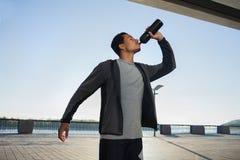 Eau potable d'homme sportif afro-américain dans la ville Image stock
