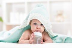 Eau potable de bébé adorable d'enfant de bouteille photographie stock libre de droits