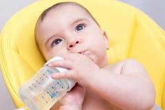 Eau potable de bébé mignon d'une bouteille images stock