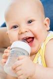 Eau potable de bébé mignon de bouteille Photographie stock libre de droits