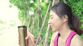 Eau potable de belle jeune femme asiatique en bonne santé de coureur parce que la sensation a fatigué après fonctionnement sur la banque de vidéos