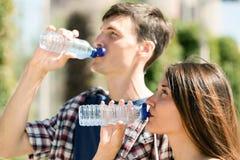 Eau potable de couples heureux des bouteilles en plastique Photographie stock libre de droits