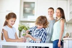 Eau potable de deux enfants avec la chaux fraîche Photos libres de droits