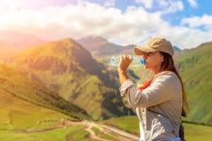 Eau potable de femme à la lumière du soleil d'été images stock