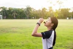 Eau potable de femme asiatique après exercice courant au jardin dans le coucher du soleil Photo libre de droits