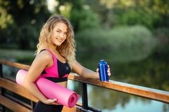 Eau potable de femme de coureur de forme physique en parc Fille d'athlète faisant une pause pendant la course à l'hydrate pendant Photos libres de droits