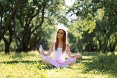Eau potable de femme en bonne sant? d'une bouteille et se reposer sur une herbe apr?s yoga d'exercice et de pratique au parc photographie stock