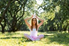 Eau potable de femme en bonne sant? d'une bouteille et se reposer sur une herbe apr?s yoga d'exercice et de pratique au parc images stock