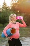 Eau potable de femme enceinte après forme physique photos stock