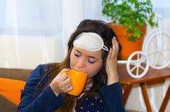 Eau potable de femme ivre dans une tasse orange, après une partie, concept de gueule de bois Image stock
