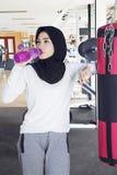 Eau potable de femme musulmane au centre de gymnase photo libre de droits