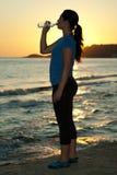 Eau potable de femme par coucher du soleil images stock