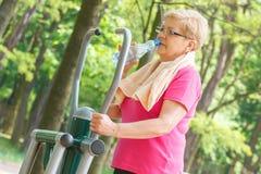 Eau potable de femme supérieure après exercice sur le gymnase extérieur, mode de vie sain Photographie stock libre de droits