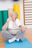 Eau potable de femme supérieure sur le tapis d'exercice Photographie stock