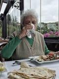 Eau potable de femme supérieure tout en prenant le déjeuner dans un restaurant Image libre de droits