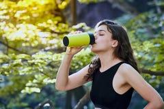 Eau potable de fille en bonne santé de forme physique de bouteille verte dans forrest photos stock