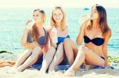 Eau potable de filles sur la plage Images stock