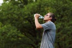 Eau potable de jeune sportif beau hors de bouteille après séance d'entraînement courante au parc public Faire la pause après séan images stock