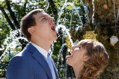 Eau potable de jeunes couples de mariage de fontaine en parc Photo stock