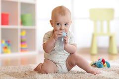 Eau potable de joli bébé garçon de bouteille Enfant s'asseyant sur le tapis dans la crèche à la maison L'enfant de sourire est 7  Photographie stock libre de droits