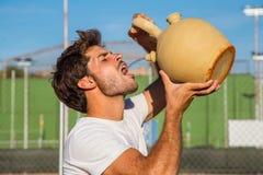 Eau potable de joueur de tennis de pot Photos stock