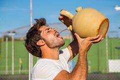 Eau potable de joueur de tennis professionnel sur la cour Photo stock