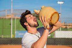 Eau potable de joueur de tennis professionnel sur la cour Images libres de droits