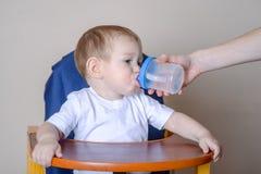 Eau potable de petit bébé garçon tout en se reposant sur une chaise dans la cuisine Maman donnant une bouteille en plastique dans photo libre de droits