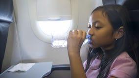 Eau potable de petite fille dans l'avion Images stock