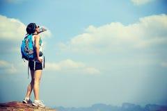 Eau potable de randonneur de femme à la montagne de coucher du soleil Image stock