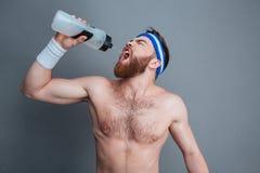 Eau potable debout et d'athlète barbu sans chemise de jeune homme Images libres de droits