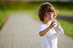 Eau propre potable de petite fille de bouteille image libre de droits