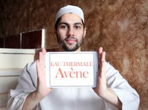 Eau thermale avene cosmetics brand logo. Logo of eau thermale avene cosmetics brand on samsung tablet holded by arab muslim man Stock Photos