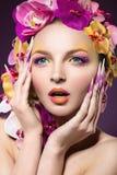 Eautiful-Frau mit dem Haar hergestellt von den Blumen und von den langen Nägeln Stockbilder