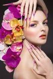 Eautiful-Frau mit dem Haar hergestellt von den Blumen und von den langen Nägeln Lizenzfreie Stockfotografie