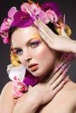 Eautiful-Frau mit dem Haar hergestellt von den Blumen und von den langen Nägeln Stockbild