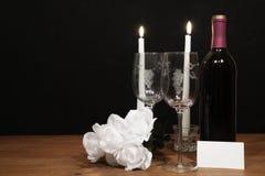 Eautiful gravou vidros de vinho e garrafa do vinho tinto, das velas brancas e das rosas brancas na tabela de madeira com a etique foto de stock royalty free