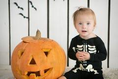 eautiful kleines Mädchen mit Down-Syndrom, das nahe einem Kürbis auf Halloween sitzt, kleidete als Skelett an lizenzfreie stockbilder