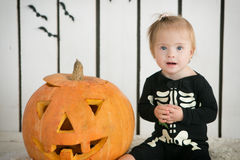 Eautiful little girl with Down syndrome sitting near a pumpkin on Halloween dressed as a skeleton Royalty Free Stock Images